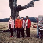 The four Beatles standing in front of a tree, next to their piano in a large field in Knole Park, Sevenoaks