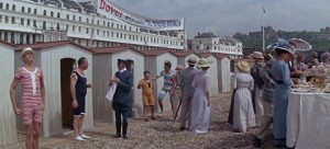 Dover beach huts on the pebbles, men and women are waiting outside