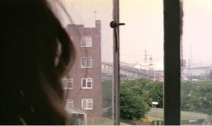 Zoe looking out of her window onto the estate- a block of flats and pylons can be seen