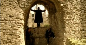 A man standing in the hole of Rochester castle grounds wall- looking out towards the cathedral