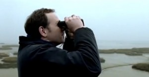 a man looking into a pair of binoculars towards the water