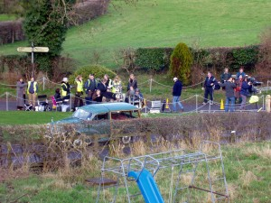 Eastenders behind the scenes - camera crew and actors on the country road behind a blue car.