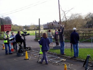 Eastenders behind the scenes - camera crew and actors on a country road with fields and fences behind them