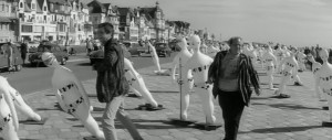 Herne Bay beach and promenade with two crew members walking through a row of white dummies