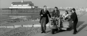 a man riding a bike and trailer down herne bay promenade, two men stand next to him whilst a women is sat on the trailer. The pier and beach can be seen behind.