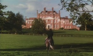 A man on a horse riding towards a county house