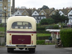 Image of the back of a cream and red van on a road with gardens behind