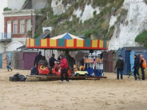 Fairground ride on a sandy beach with white cliffs behind