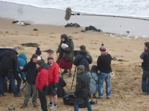 Camera crew on a sandy beach woth the sea behind