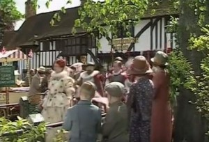 Chilham village with lots of cast members walking around in front of a tudor style house