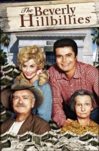 The Beverly Hillbillies poster- 4 cast members smiling at the camera in front of a doorway. The Beverly Hillbillies  written on a wooden sign above