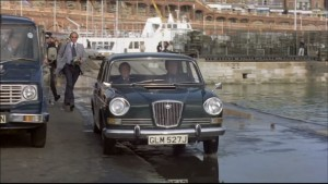 A black classic car parked at Ramsgate Harbour with cast members walking towards it, Boats and sea can be seen behind