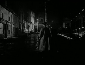 Gravesend street at night with a man in a trench coat walking away from the camera down the middle