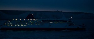 The White Cliffs of Dover at night with a ferry in the sea in front