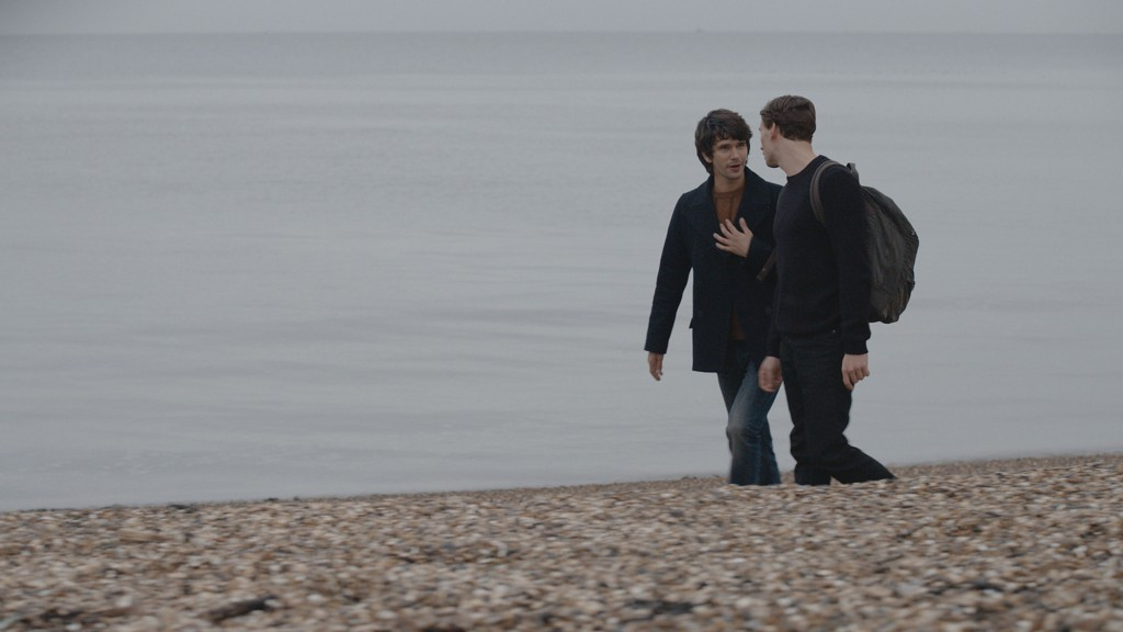 Danny (BEN WHISHAW) and Alex (EDWARD HOLCROFT) walking along a beach