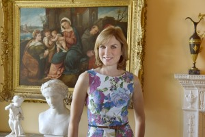Antiques Roadshow - Fiona Bruce standing in front of a painting and antiques