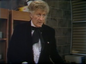 Jon Pertwee as Dr Who in a suit in an office with a brick wall