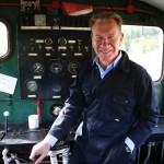 Michael Portillo standing on a steam train