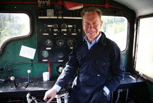 Michael Portillo standing on a steam train in front of the control panel