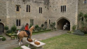 The Royals screenshot at Allington Castle - a woman riding a horse into a castle