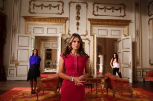 Victoria Ekanoye (Rachel, left), Elizabeth Hurley (Queen Helena, center) and Alexandra Park (Princess Eleanor, right) standing in a grand living room with white and gold walls