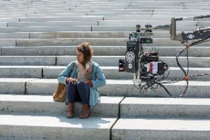 Behind the scenes of The Tunnel Sabotage Angel Coulby sitting on some steps with cameras filming