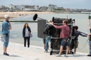 Behind the scenes of The Tunnel Sabotage - cameras filming on a coastal promenade
