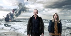 Stephen Dillane and Clémence Poésy walking along a beach towards the camera away from a burning plane