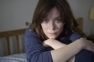Anna Friel as Marcella sitting on a bed hugging her knees