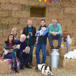 The Countyfile presenters on bails of hay L-R - Anita Rani, Ellie Harrison, John Craven, Adam Henson, Matt Baker, Peg, Tom Heap