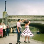 two actors dancing on maidstone bridge next to the river.