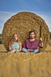 two actors sitting in front of a hay bail. The Male has a gun.