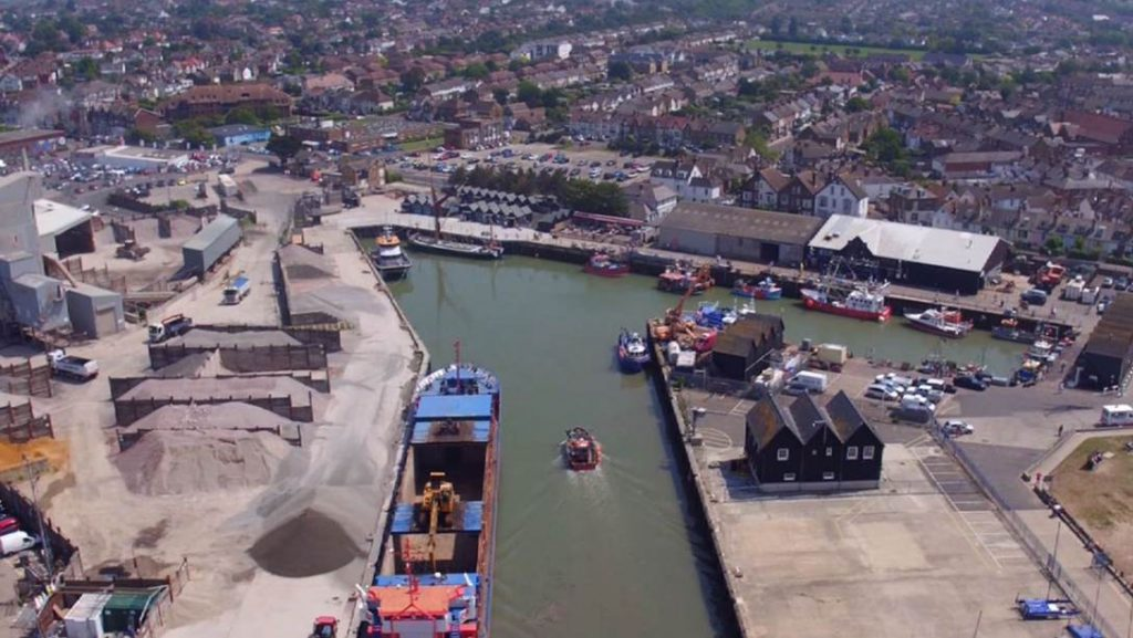 Whitstable harbour drone shot of harbour with boats in, town can be seen in background.
