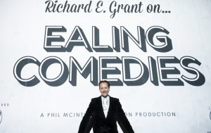Richard E. Grant standing in front of a white background, writing says Richard E Grant on...Ealing Comedies
