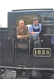 Richard E. Grant on the Kent and East Sussex Railway leaning through the window of a stream train with the driver