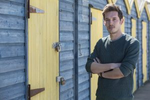 Humans Ed (Sam Palladio) standing in front of beach huts at Westgate-on-Sea