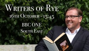 Writer sitting down with a book laughing away from the camera. Writers of Rye 16th Octover 15:45 BBC ONE South East written in white.