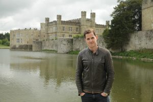 Dan Jones standing in front of the water at Leeds Castle with the castle in the background.