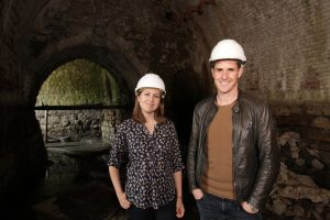 Dan Jones and Elizabeth Norton standing in an underground passage at Leeds Castle