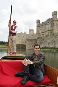Dan Jones sitting on a boat on the water in front of Leeds Castle.