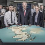 Hunted HQ team standing at a map of the UK