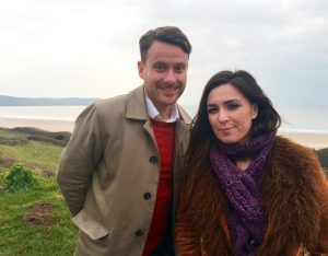 Presenters Kerr Drummond and Sara Damergi standing in the countryside with the sea in the background