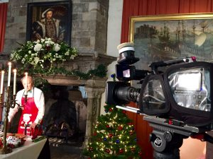 Behind the scenes at Leeds Castle - presenter in apron being filmed in front of a fireplace