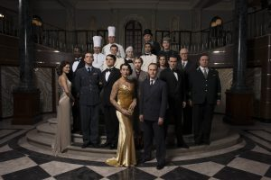The Halcyon cast standing in a hall on a small staircase,