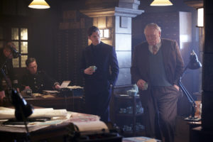 Archer (Sam Riley) and Harry Woods (James Cosmo) standing in an office room