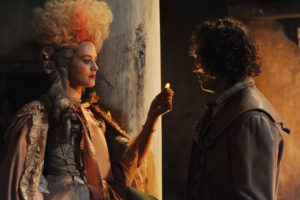 Charlotte Wells (Jessica Brown Findlay) in period costume, handing something small to Daniel Marney (Rory Fleck-Byrne)