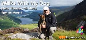 Image of presenter kneeling down with his dog. Mountains and a river can be seen behind. Walks with my dog reads on the top