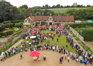 Raised view of Ightham House and gardens with people walking around stalls