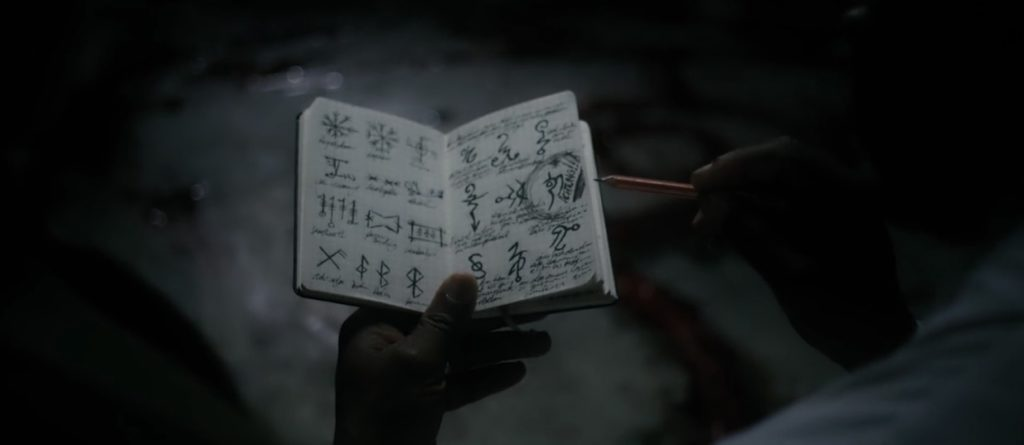 Hand holding open book of arcane symbols