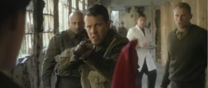 Lieutenant Conner Taylor (Lee Latchford-Evans) pointing rifle towards figure in the foreground.